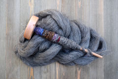 Wood drop spindle on a pile of wool roving twisted with yarn Royalty Free Stock Photos