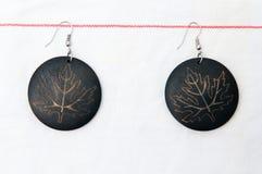 Wood earings. Handmade wood earings on a white fabric Stock Photo