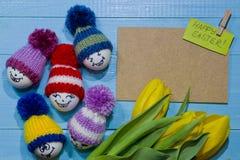 wood easter ägg Emoticons i stucken hatt med pom-poms Ett b Arkivbild