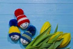 wood easter ägg Emoticons i stucken hatt med pom-poms Ett b Arkivfoto