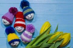 wood easter ägg Emoticons i stucken hatt med pom-poms Ett b Royaltyfri Foto