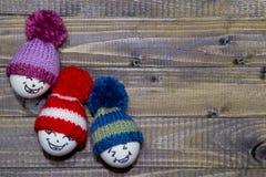 wood easter ägg Emoticons i stucken hatt med pom-poms han Royaltyfri Bild