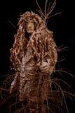 Wood elakt troll med ett träd i händer på en svart bakgrund Royaltyfri Fotografi