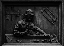 Wood engraving showing a carpenter at work. Shot in black and white detail of the sculpture on the facade of this historic building representing some characters Stock Images