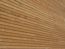 Wood façade. Background texture of finely slatted natural brown wood in a parallel pattern used in building decor and construction Stock Photography