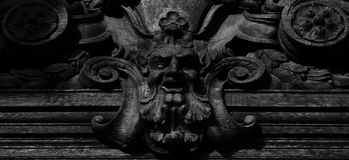Wood face on the main facade. Shot in black and white detail of the sculpture on the facade of this historic building representing some characters / animals / royalty free stock photo
