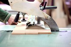 Wood factory worker cutting wood boards with sliding saw Royalty Free Stock Photo