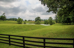 Wood fence along the grass and clouds. Country field of Upperville Virginia with green grass, fence, trees, and clouds Stock Image