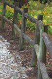 Wood fence at garden. A pine wood fence with coloured flowers and vegetation in a garden in S Pedro de Moel - a beach in Portugal Stock Photo