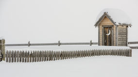 Wood fence leads to a snow covered outhouse Royalty Free Stock Images