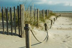 Wood fence and rope fence on beach with sand and seat oats Royalty Free Stock Photo