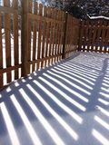 Wood fence shadow in snow. Dramatic shadow of a garden backyard fence with the long shadows or late day in the winter snow Stock Photo