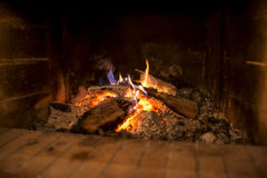 Wood fire burning in a brick hearth Stock Image