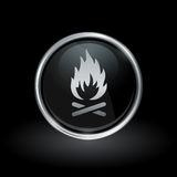 Wood fire icon inside round silver and black emblem. Burning symbol with wood fire icon inside round chrome silver and black button emblem on black background Royalty Free Stock Photo
