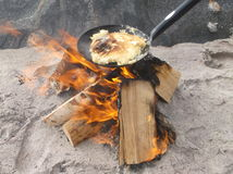 Wood fire. Making pancakes on the beach Stock Photography