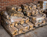 Wood For The Fire For Sale. Fire Wood For Sale On Concrete Walk Way in neat stacks of  bundles in Plastic Royalty Free Stock Photography