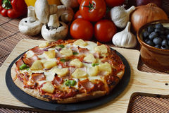 Wood Fired ham and pineapple supreme Pizza. Wood Fired Gourmet pizza with a topping of Ham and Pineapple Royalty Free Stock Images