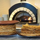 Wood fired oven and seasoned flatbreads stock images