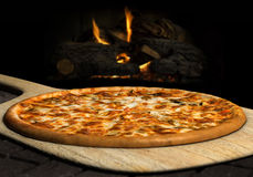 Wood Fired Pizza. Pizza resting on a pizza peel near an open fire Royalty Free Stock Image