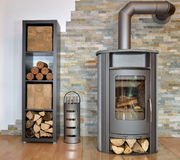 Wood fired stove. With fire-wood, fire-irons, and briquettes from bark bevore ignition Stock Image
