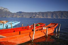 Wood fishing boat fisher orange color Floating on blue water Lugu lake scenic spot surrounded by snow mountain and high sky stock photography