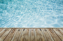 Wood floor beside the blue crystal clear water. Royalty Free Stock Photography
