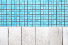 Wood floor beside the blue swimming pool Royalty Free Stock Images