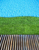Wood floor and grass beside the blue swimming pool Stock Photo