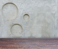 Wood floor and gray concrete wall with circle pitted texture bac Royalty Free Stock Image