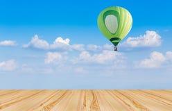 Wood floor and hot air balloon on blue sky. Wood floor and green hot air balloon with blue sky background Royalty Free Stock Photos