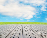 Wood floor with meadow, cloud and blue sky Royalty Free Stock Photos