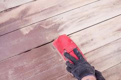 Wood floor polishing maintenance work by grinding machine. Men`s hands with gloves make repairs at home. Grinding. Wood floor polishing maintenance work by royalty free stock image
