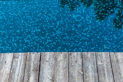 Wood floor beside pool Royalty Free Stock Image