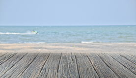 Wood floor on sand beach and tropical sea with blur jet ski solf focus Royalty Free Stock Images