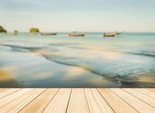Wood floor top on blue sea in morning light. Wood floor top on blurred blue sea with sand beach and blue sky in morning light Royalty Free Stock Image