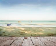 Wood floor top on blue sea in morning light. Wood floor top on blurred blue sea with sand beach and blue sky in morning light Stock Photography