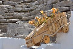 Wood flowerpot with colorful flowerson old exterior stone house royalty free stock photography