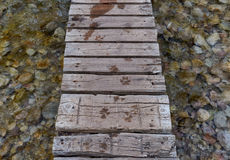 Wood footbridge over a river. With wet dog tracks Royalty Free Stock Photos