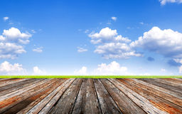 Wood foregroung and landscape of green field under blue sky and Royalty Free Stock Images