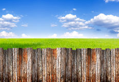 Wood foregroung palisade and landscape of green field under blue Royalty Free Stock Images