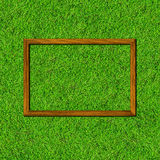 Wood frame on green grass field Stock Photos