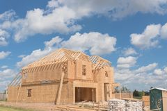 Wooden frame house under construction Pearland, Texas, USA. Wood frame house under construction and cloud blue sky in suburban Pearland, Texas, USA. New stick stock photo