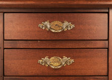 Wood furniture. Detail of closed drawers with ornate brass handl Royalty Free Stock Image