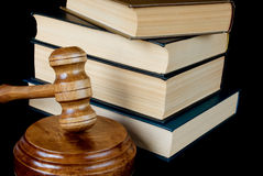 Wood gavel, soundblock and stack of thick old books Stock Photo