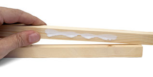 Wood and glue. Man hand holding wood stick with white glue stock images
