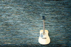 Wood guitar against wall. Background and texture stock photos