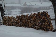 Wood hög som täckas av snö under en snöstorm som väntar för att brännas Arkivfoto
