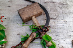 Wood hammer and sickle. Wooden hammer and the sickle are bound with an iron chain Royalty Free Stock Photos