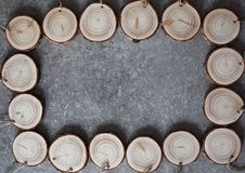 Wood handmade medals with linen twine. Natural wood handmade medals with linen twine. Stack of wooden homemade medals on grey grunge table. Round wood slices Stock Image