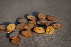 Runes on sand. Wood handmade runes and minerals on the sand Royalty Free Stock Photography
